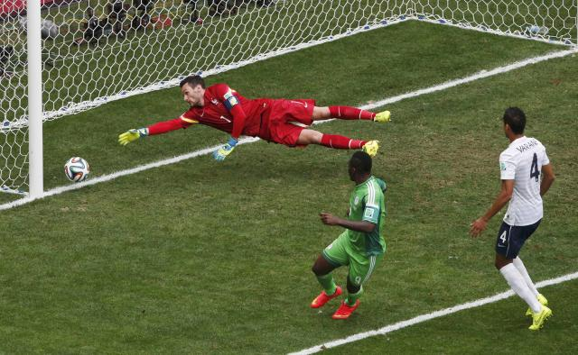Nigeria's Emmanuel Emenike (C) kicks to score a goal against France's goalkeeper Hugo Lloris (L), which was later ruled offside and disallowed, during their 2014 World Cup round of 16 game at the Brasilia national stadium in Brasilia June 30, 2014. REUTERS/David Gray (BRAZIL - Tags: SOCCER SPORT WORLD CUP)