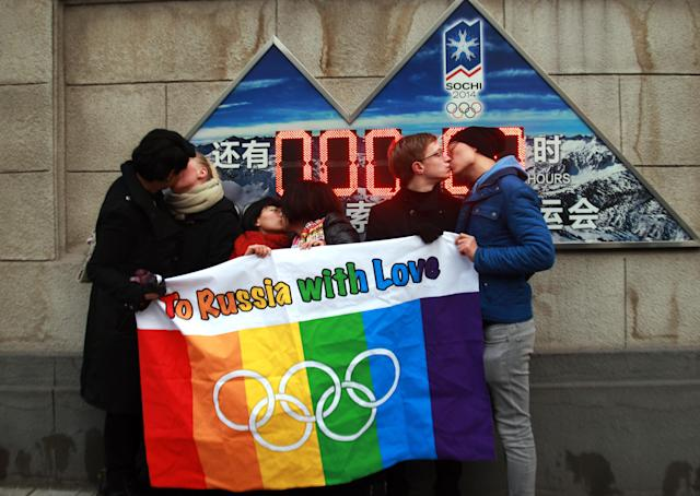 A group of gay and lesbian activists hold a banner of the rainbow flag, the Olympic rings and the words 'To Russia with love' as they stage a Valentine's Day kissing protest in Beijing on Feb. 14, 2014. (STR via Getty Images)