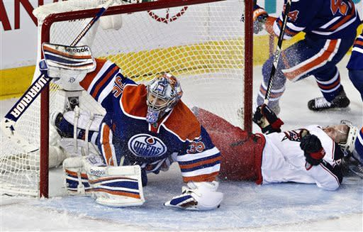 Columbus Blue Jackets' Sean Collins (43) crashes into Edmonton Oilers goalie Nikolai Khabibulin (35) during the second period of their NHL hockey game, Thursday, March 28, 2013, in Edmonton, Alberta. (AP Photo/The Canadian Press, Jason Franson)