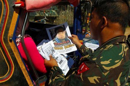 Soldiers distribute pictures of a member of extremist group Abu Sayyaf Isnilon Hapilon, who has a U.S. government bounty of $5 million for his capture, in Butig, Lanao del Sur
