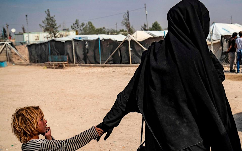 A picture taken on October 17, 2019 shows a French citizen holding a child by the hand at the Kurdish-run al-Hol camp for the displaced where families of Islamic State (IS) foreign fighters - AFP