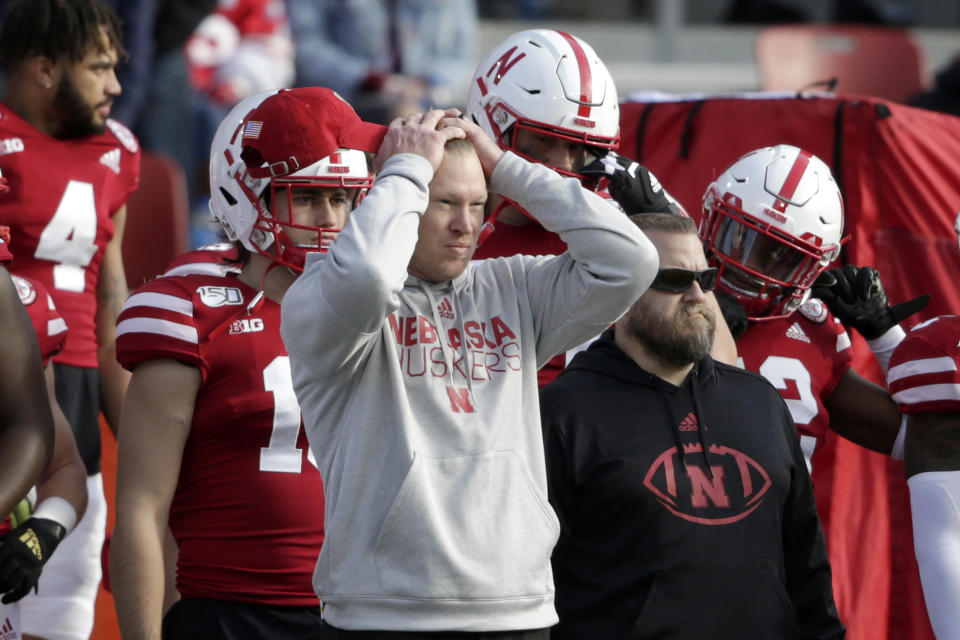 FILE - In this Nov. 16, 2019, file photo, Nebraska head coach Scott Frost holds his head during the closing seconds of an NCAA college football game against Wisconsin in Lincoln, Neb. Wisconsin won 37-21. The coach is frustrated, not just by the global pandemic that has disrupted life for everyone, but by associated factors that have kept the Huskers from playing. Some teams in the country already have played seven or even eight games.(AP Photo/Nati Harnik, File)