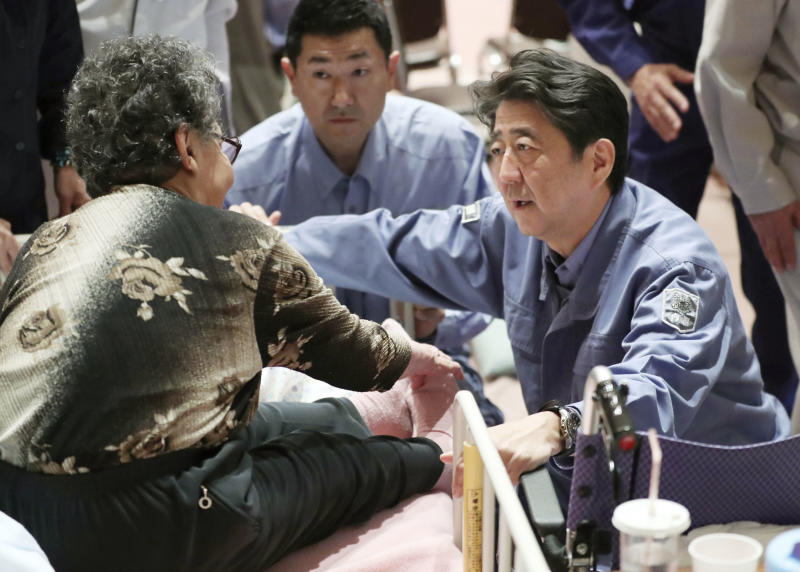 Japan's Prime Minister Shinzo Abe, right, talks with an elderly woman at a shelter as Abe visits the site of a landslide triggered by the Sept. 6, earthquake in Abira, Hokkaido, northern Japan Sunday, Sept. 9, 2018. Japanese authorities say dozens of people have been confirmed dead from a powerful earthquake that struck the northern island of Hokkaido last week. (Kyodo News via AP)