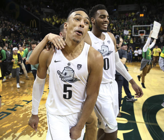 Oregon's Elijah Brown, left, and Troy Brown Jr. celebrate after Oregon defeated Arizona 98-93 in overtime, as fans run onto the court after an NCAA college basketball game Saturday, Feb. 24, 2018, in Eugene, Ore. (AP Photo/Chris Pietsch)