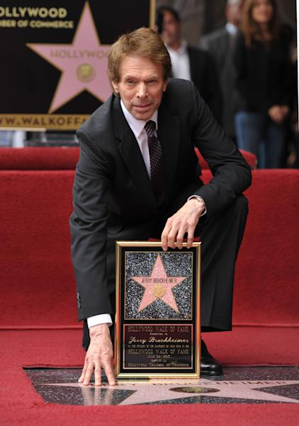 "In this June 24, 2013 file photo, film producer Jerry Bruckheimer poses with his star on the Hollywood Walk of Fame in Los Angeles. After more than two decades with Disney, where he produced the juggernaut ""Pirates of the Caribbean"" and ""National Treasure"" film franchises among many box-office hits, Bruckheimer begins a new partnership with Paramount in March 2014. Bruckheimer continues his work in television, too, where he's found groundbreaking success with the many ""CSI"" series and ""The Amazing Race,"" which has won 14 Emmy Awards. (Photo by John Shearer/Invision/AP, File)"