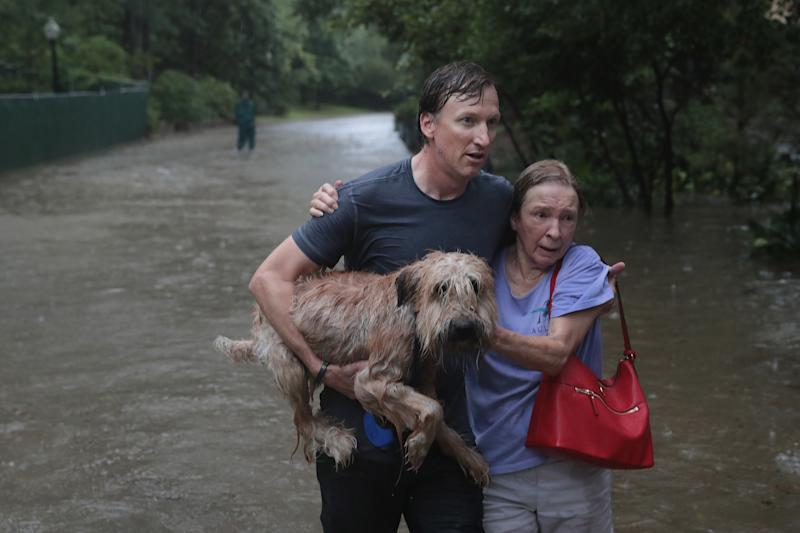 Andrew White (left) helps a neighbor down a street after rescuing her in his boat in Houston's River Oaks neighborhood. (Scott Olson via Getty Images)