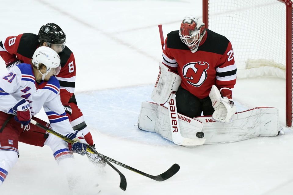 New York Rangers center Brett Howden (21) shoots as New Jersey Devils goaltender Mackenzie Blackwood (29) makes a save with Devils defenseman Will Butcher (8) looking on during the first period of an NHL hockey game, Tuesday, April 13, 2021, in Newark, N.J. (AP Photo/Kathy Willens)