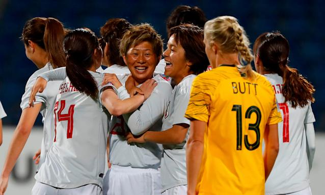 Kumi Yokoyama celebrates after her late goal for Japan while Tameka Butt looks dejected for Australia.