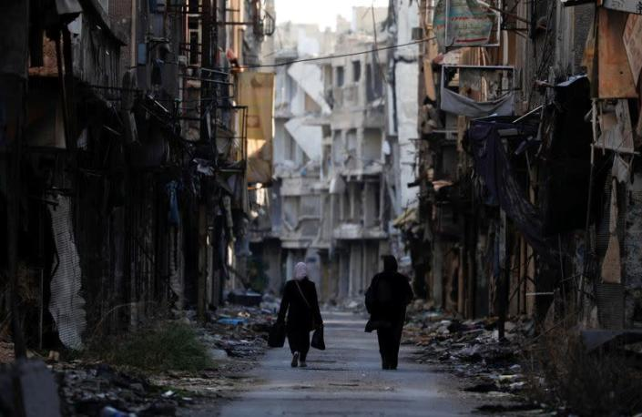 FILE PHOTO: Women walk past damaged buildings at the Yarmouk Palestinian refugee camp on the southern outskirts of Damascus