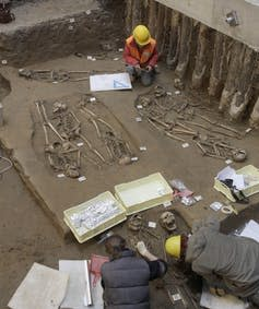 people excavating human skeletons from ground