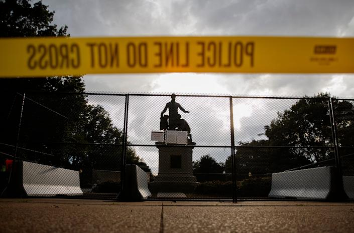 Yellow police tape, concrete barricades and fencing surround the Emancipation Memorial in Lincoln Park in Washington, Thursday, June 25, 2020. The Emancipation Memorial depicts a freed slave kneeling at the feet of President Abraham Lincoln. Calls are intensifying for the removal of the statue as the nation confronts racial injustice.