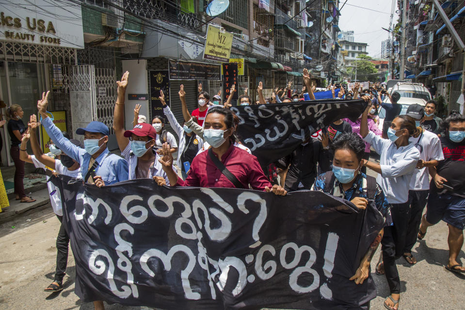 """Anti-coup protesters hold a banner that reads """"What are these? We are Yangon residents!"""" as they march during a demonstration in Yangon, Myanmar on Tuesday April 27, 2021. Demonstrations have continued in many parts of the country since Saturday's meeting of leaders from the Association of Southeast Asian Nations, as have arrests and beatings by security forces despite an apparent agreement by junta leader Senior Gen. Min Aung Hlaing to end the violence. (AP Photo)"""