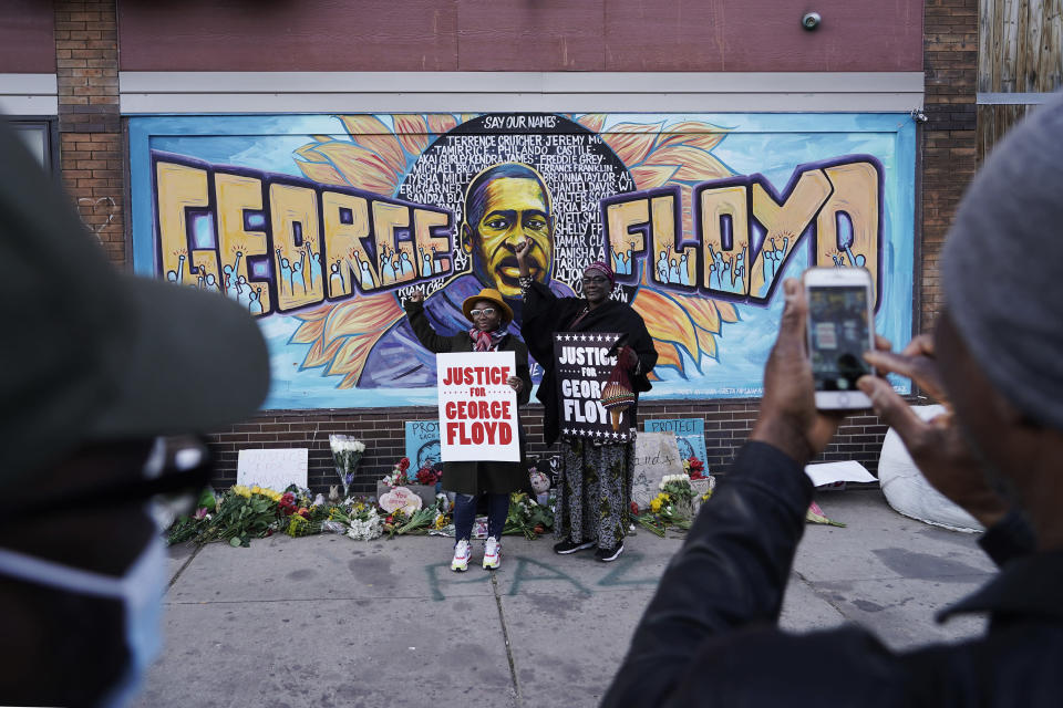 People pose for pictures in front of a mural for George Floyd after a guilty verdict was announced at the trial of former Minneapolis police Officer Derek Chauvin for the 2020 death of Floyd, Tuesday, April 20, 2021, in Minneapolis, Minn. (AP Photo/Morry Gash)
