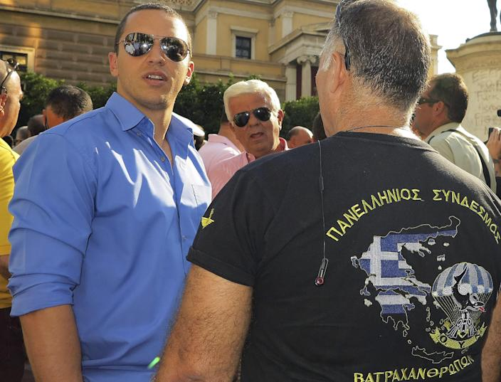 FILE - In this Sept. 12, 2012 file photo, extreme right Golden Dawn party spokesman Ilias Kassidiaris, left, speaks with a retired special force military officer during a protest in Athens. Kassidiaris was arrested Saturday, Sept. 28, 2013, on charges of forming a criminal organization. Greek police also confirmed the arrest of the party leader Nikos Mihaloliakos on the same charges. (AP Photo/Dimitri Messinis, File)