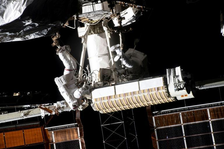 French astronaut Thomas Pesquet (L) installs a solar panel on the International Space Station on June 20, 2021