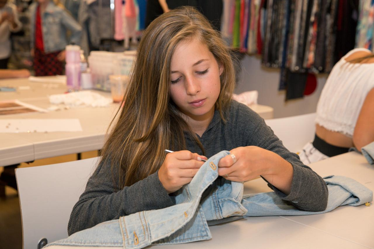 <p>A camper works diligently to create a denim jacket with colorful stitching.</p>