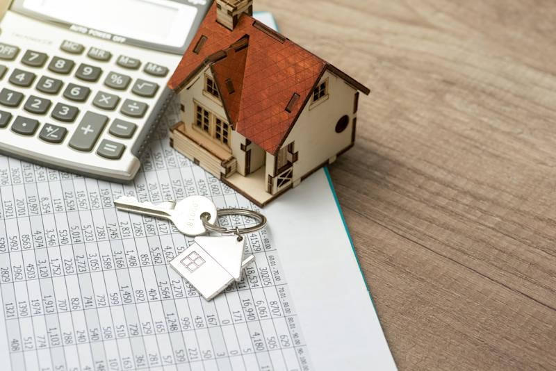 House resting on calculator concept for mortgage calculator, home finances or saving for a house. Photo: Getty
