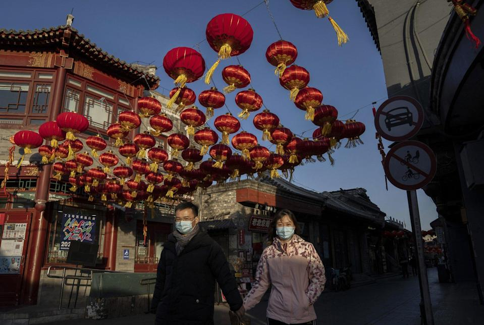 A couple walks under traditional red lanterns hung for Spring Festival in Beijing, China. Photo: Getty Images