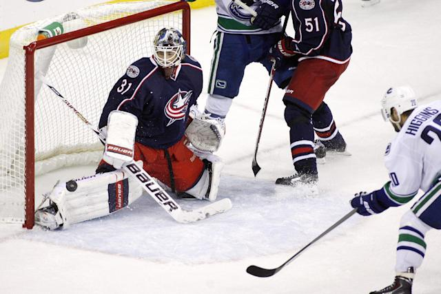 Columbus goalie Curtis McElhinney (31) blocks a shot in the final minute by Vancouver's Chris Higgins, right, during an NHL hockey game Sunday, Oct. 20, 2013, in Columbus, Ohio. (AP Photo/ Mike Munden)