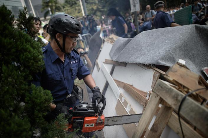 Police use a chainsaw to remove barricades erected by pro-democracy protesters in the Admiralty district of Hong Kong on October 14, 2014 (AFP Photo/Ed Jones)