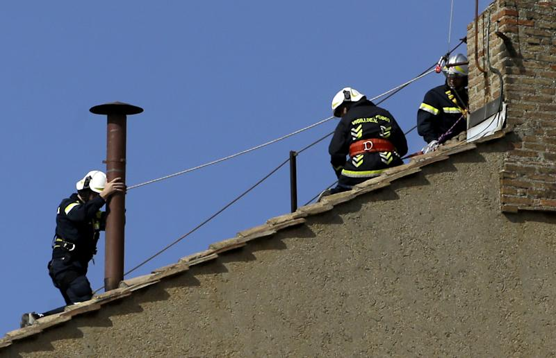 Firefighters place the chimney on the roof of the Sistine Chapel, where cardinals will gather to elect the new pope, at the Vatican, Saturday, March 9, 2013. The preliminaries over, Catholic cardinals are ready to get down to the real business of choosing a pope. And even without a front-runner, there are indications they will go into the conclave Tuesday with a good idea of their top picks. The conclave date was set Friday during a vote by the College of Cardinals, who have been meeting all week to discuss the church's problems and priorities, and the qualities the successor to Pope Benedict XVI must possess. (AP Photo/Gregorio Borgia)