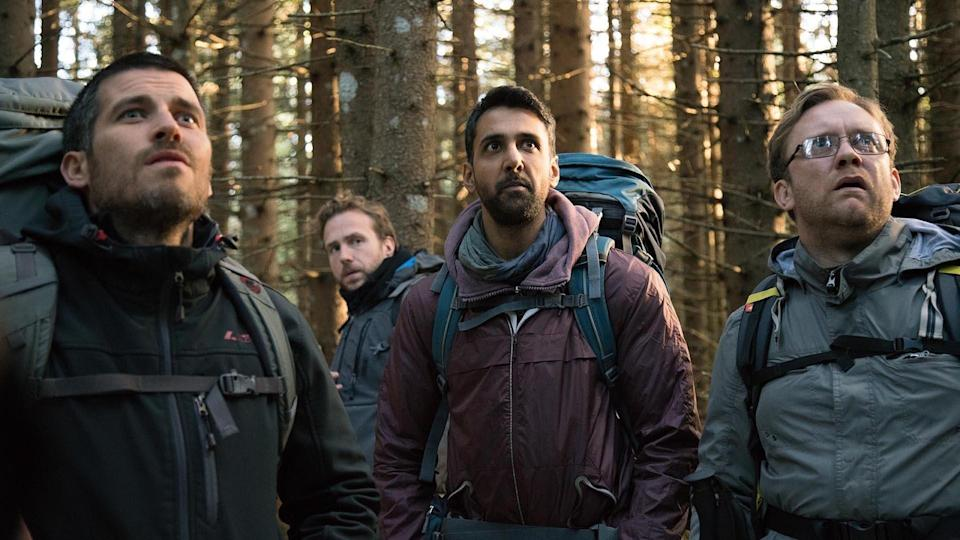 A still from the ritual shows four men looking scared in the woods