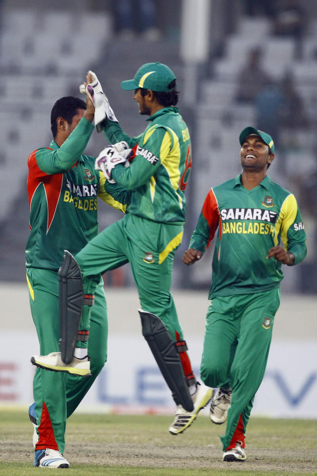 Bangladesh's Mahmudullah, left, Anamul Haque, center, and Shuhag Gazi celebrate the dismissal of Sri Lanka's Lahiru Thirimanne on the third one day international cricket match against Bangladesh in Dhaka, Bangladesh, Saturday, Feb. 22, 2014. (AP Photo/A.M. Ahad)