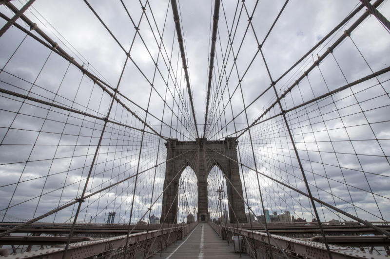 The Brooklyn Bridge walkway is empty of pedestrians and cyclists, Friday, April 10, 2020, in New York. The new coronavirus causes mild or moderate symptoms for most people, but for some, especially older adults and people with existing health problems, it can cause more severe illness or death. (AP Photo/Mary Altaffer)