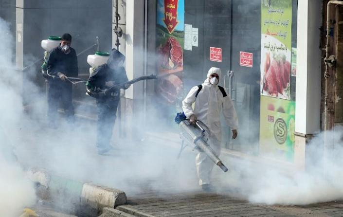 Iranian firefighters and municipality workers disinfect streets in the capital Tehran in a bid to halt the wild spread of coronavirus (AFP Photo/STR)
