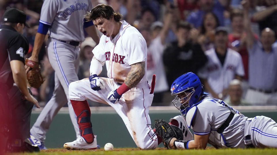 Boston Red Sox's Jarren Duran celebrates after scoring on his RBI triple and an error by the Toronto Blue Jays during the fourth inning of the second baseball game of a doubleheader at Fenway Park, Wednesday, July 28, 2021, in Boston. At right is Blue Jays catcher Reese McGuire. (AP Photo/Charles Krupa)