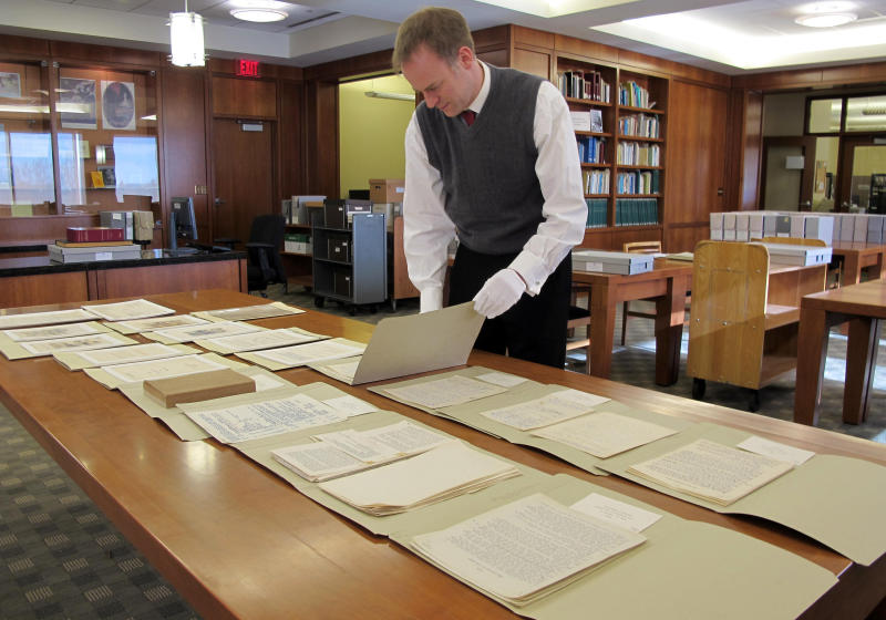 """In this Nov. 27, 2012 photo Marquette University Archivist Bill Fliss arranges some of the 11,000 J.R.R. Tolkien papers the university owns in the library of the Milwaukee school _ home to the largest Tolkien collection in the world. Marquette offered it's first class on J.R.R. Tolkien during the fall semester as part of their anniversary celebration of the 75th anniveresary of the """"The Hobbit"""" being published. When """"The Hobbit"""" movie opens Friday, the 32 students in the class will be nearly experts on J.R.R. Tolkien. (AP Photo/Carrie Antlfinger)"""