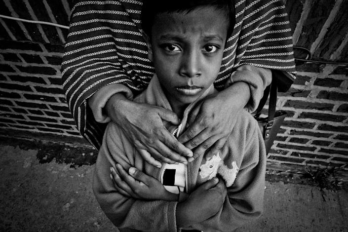<p>Eight-year-old Iman Hossain in the arms of his mother, Shamima Akhter, in November 2015 in Jackson Heights, Queens, N.Y. They had been in the United States for a few months. They settled in Jackson Heights because they have relatives in Queens. (Photo: Yunghi Kim/Contact Press Images) </p>