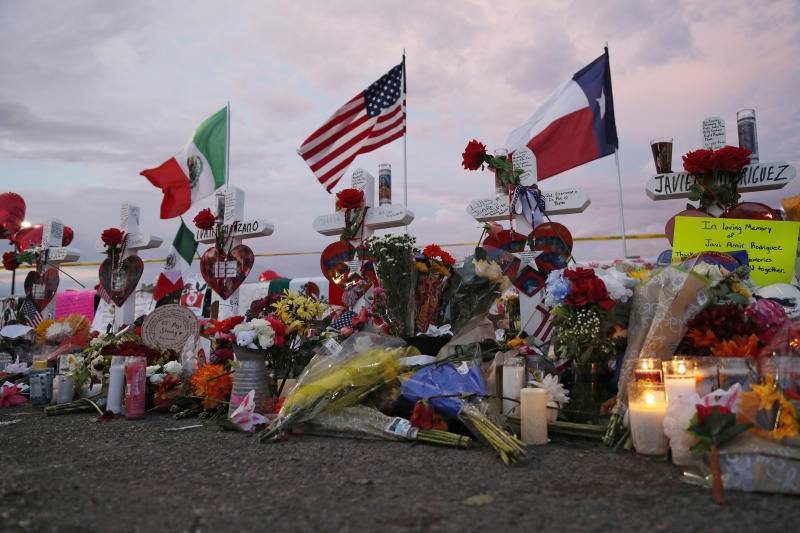 Flags fly over crosses at a makeshift memorial near the scene of a mass shooting at a shopping complex Tuesday, Aug. 6, 2019, in El Paso, Texas. The border city jolted by a weekend massacre at a Walmart absorbed more grief Monday as the death toll climbed and prepared for a visit from President Donald Trump over anger from El Paso residents and local Democratic leaders who say he isn't welcome and should stay away.  (AP Photo/John Locher)