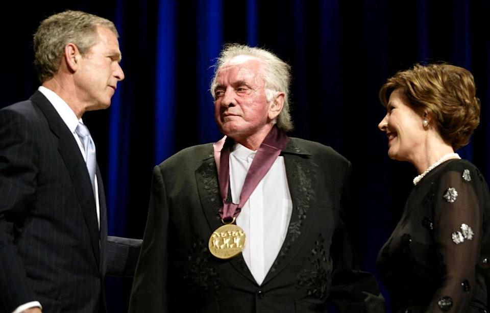 Country legend Johnny Cash, who will be honored with a statue representing Arkansas in the US Capitol, is congratulated on an award in 2002 by then president George W. Bush and first lady Laura Bush (AFP Photo/STEPHEN JAFFE)