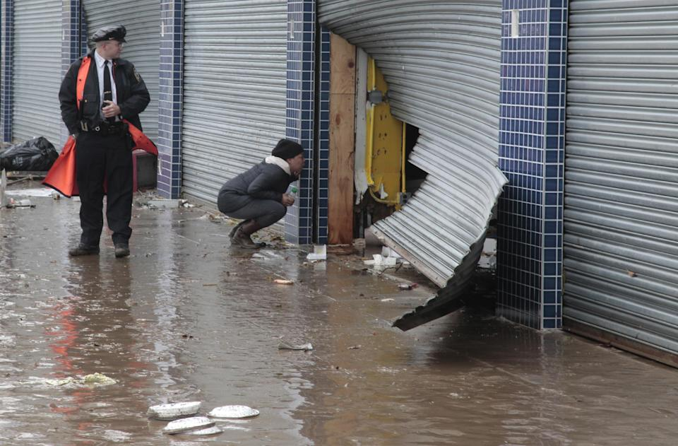 A police officer watch as a passerby look into a store through a damaged security grate, in the aftermath of Hurricane Sandy on Tuesday, Oct. 30, 2012, on Mermaid Avenue in Coney Island, N.Y. Sandy, the storm that made landfall Monday, caused multiple fatalities, halted mass transit and cut power to more than 6 million homes and businesses.(AP Photo/Bebeto Matthews)