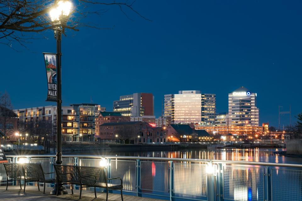 cityscape photo of a pier, lake, and buildings at River Walk Park in Wilmington, Delaware at night