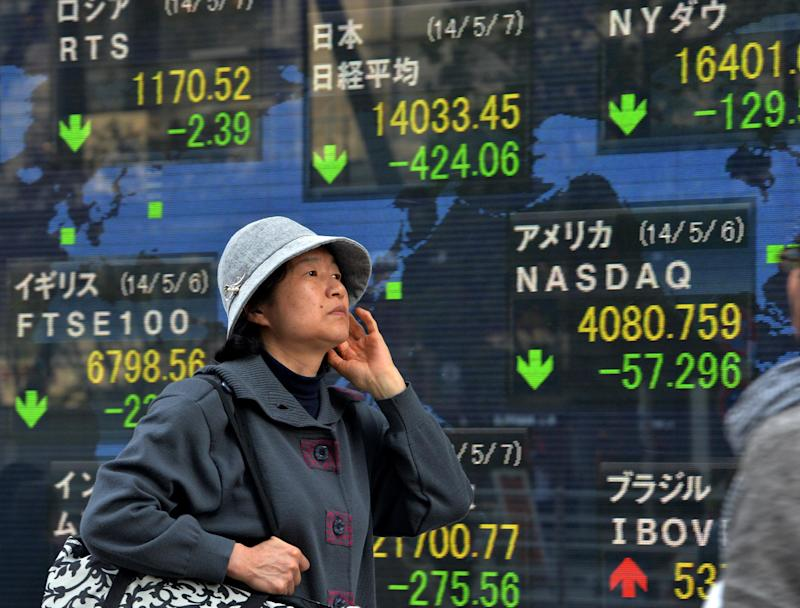 A woman passes before a share prices board in Tokyo on May 7, 2014