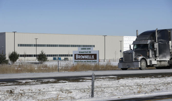 This Dec. 9, 2013 photo shows a semi-trailer truck passing the Brownells, Inc. distribution and retail facility that is nearing completion along Interstate 80, in Grinnell, Iowa. The central Iowa city of 9,100 is home to Grinnell College, the selective liberal arts institution known for its commitment to social justice. Billed as the world's largest supplier of firearms accessories, Brownells is a family-owned company that has long been based 20 miles south of Grinnell in Montezuma, Iowa. (AP Photo/Charlie Neibergall)