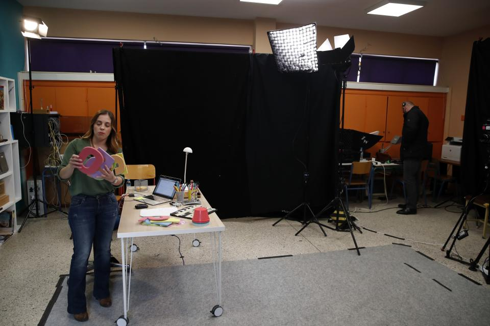 Teacher Sofia Klada prepares to record lessons that are broadcast on public television, at an elementary school in Athens, Thursday, Nov. 19, 2020. Most other European countries have vowed to keep schools open, but the pandemic has hit Greece hard for the first time in recent weeks following a successful lockdown in the spring, overwhelming hospitals in parts of the country. State television is making and broadcasting lessons, while teachers sit in empty classrooms talking to remote students. Despite some problems, they say it keeps children in touch with their schools. (AP Photo/Thanassis Stavrakis)