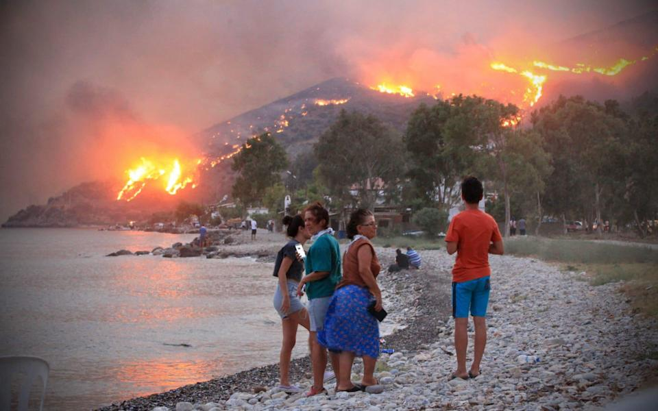 Tourists have been forced to escape on boats for safety, and dozens of villages have been evacuated as winds fan the flames. - AFP