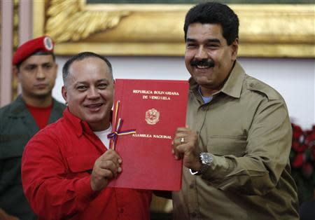 Venezuelan President Nicolas Maduro (R) receives from National Assembly President Diosdado Cabello a document approving a law which grants him with decree powers in Caracas, November 19, 2013. REUTERS/Carlos Garcia Rawlins