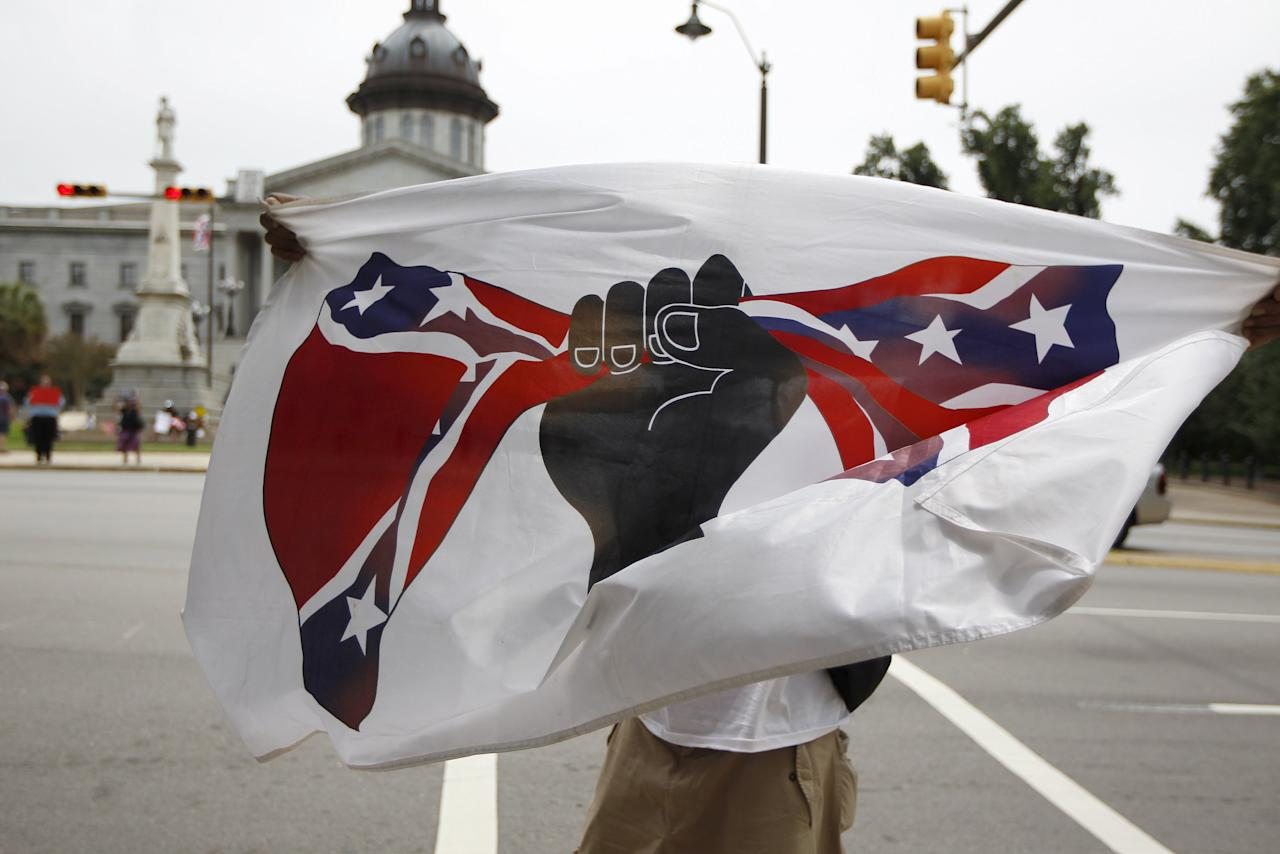 Dmitri Ford carries his own flag that opposes the confederate flag, in front of the South Carolina State House in Columbia, South Carolina July 4, 2015. South Carolina lawmakers plan to introduce a resolution on Tuesday to begin a debate on removing the Confederate flag from the State House grounds after the June 17 shooting of nine black churchgoers at a historic black church in Charleston, South Carolina. The man arrested in the shooting, Dylann Roof, is a 21-year-old white man who had posed with a Confederate battle flag in photos posted on a website that displayed a racist manifesto attributed to him. REUTERS/Tami Chappell      TPX IMAGES OF THE DAY