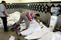 """Men check the IDs of Muslim Brotherhood supporters, shot shot in the Egyptian capital after violence erupted the night before, at a field hospital in Cairo, on July 27, 2013. The bloodshed came hours after the military-backed interior minister, Mohammed Ibrahim, warned a long-running sit-in at Cairo's Rabaa al-Adawiya mosque by Morsi loyalists would be ended """"in the framework of the law."""""""