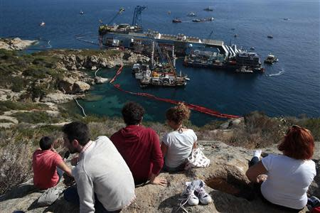 People look on as the capsized cruise liner Costa Concordia lies on its side next to Giglio Island September 16, 2013. REUTERS/Tony Gentile