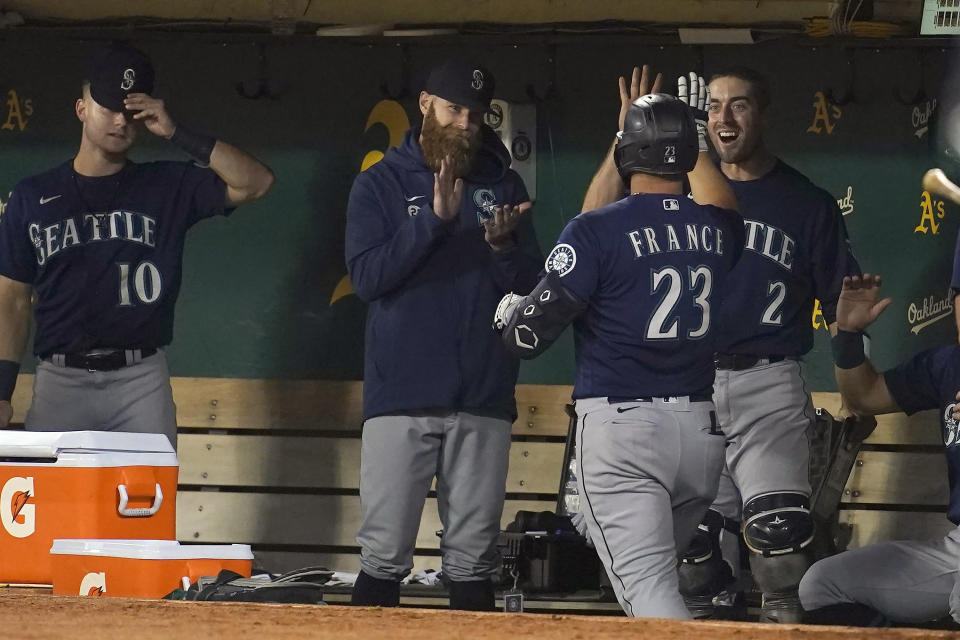 Seattle Mariners' Ty France (23) is congratulated by teammates after hitting a home run against the Oakland Athletics during the fifth inning of a baseball game in Oakland, Calif., Wednesday, Sept. 22, 2021. (AP Photo/Jeff Chiu)