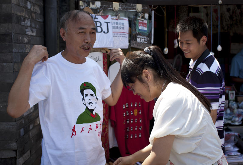 """ADDS TRANSLATION OF WRITING ON T-SHIRT - In this Sunday, July 31, 2011 photo, a Chinese man tries on a t-shirt with an image of U.S. President Barack Obama dressed in a Cultural Revolution-era military uniform, with Chinese writing reading """"Serves the People"""" at a shop in Beijing, China. Obama and Chinese President Xi Jinping face weighty issues when they meet at a private estate in California next week, but their most important task may simply be establishing a strong rapport. (AP Photo/Andy Wong)"""