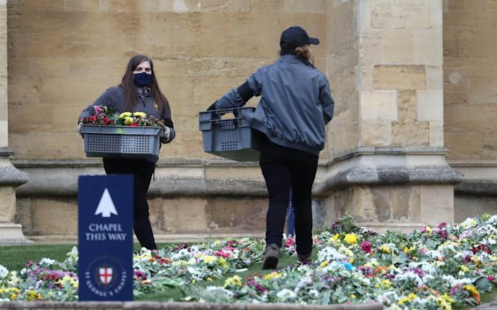 Staff place flowers on the ground outside St George's Chapel which were left by well-wishers outside Windsor Castle, Berkshire - Gareth Fuller / PA