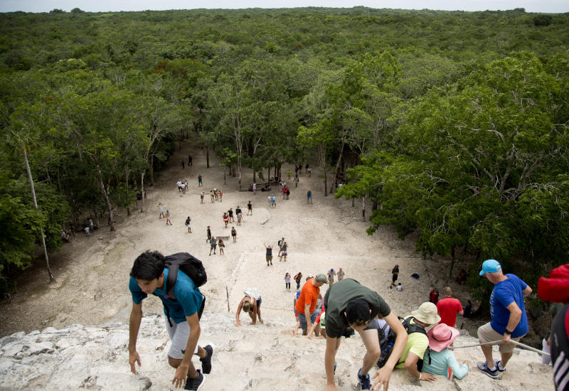 In this Aug. 1, 2018 photo, tourists climb a temple at the archeological site of Coba, in Mexico's Yucatan Peninsula. Mexico's president-elect Andres Manuel Lopez Obrador wants to build a train that would run from Yucatan Peninsula resort of Cancun to the Mayan ruins of Palenque in Chiapas, a route dotted by low jungle, wildlife reserves, pre-Hispanic archaeological sites, wetlands and underground rivers that can suddenly cave in. (AP Photo/Eduardo Verdugo)