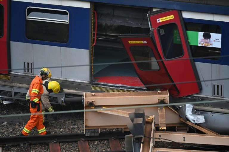 Passengers had to leave the train through a broken door and cross tracks (AFP Photo/Anthony WALLACE)