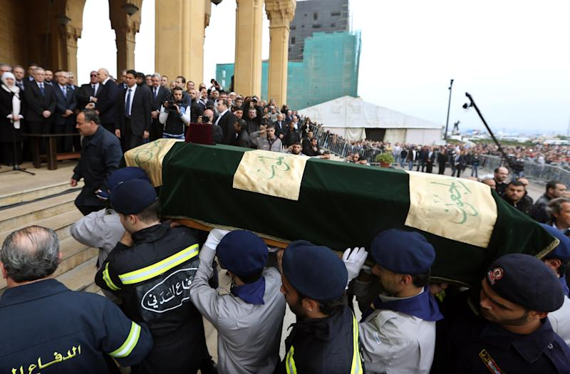 Lebanese people carry a coffin of Mohammed Chatah, a senior aide to former Lebanese Prime Minister Saad Hariri, who was assassinated on Friday by a car bomb, during his funeral procession at Martyrs' Square in Beirut, Lebanon, Sunday, Dec. 29, 2013. Angry mourners have chanted against Hezbollah as they buried the slain Lebanese politician who was critical of the Shiite militia. (AP Photo/Bilal Hussein)